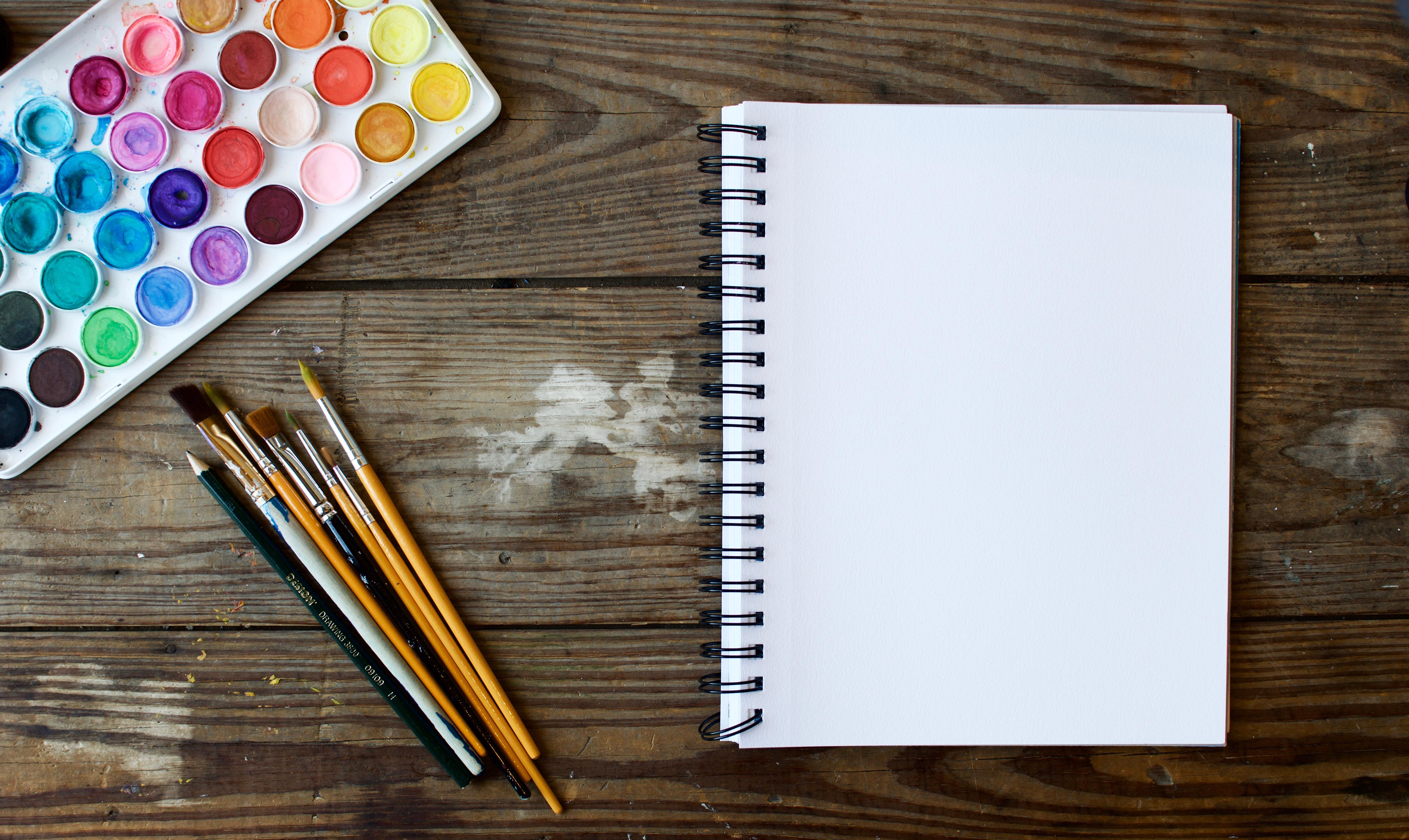blank journal ready for content with brushes and paints