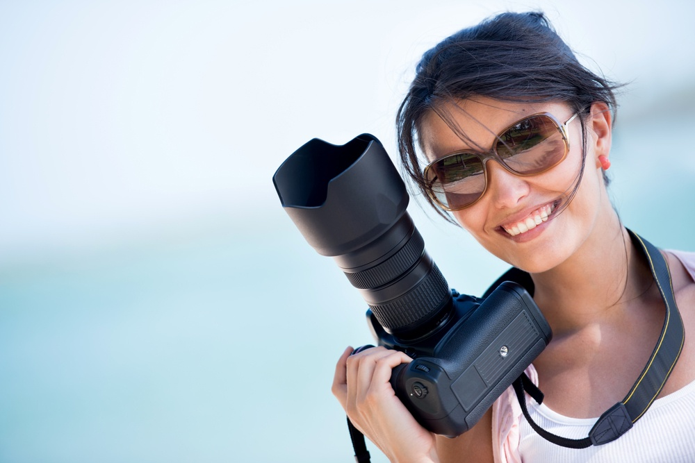 Professional female photographer holding a camera and smiling.jpeg