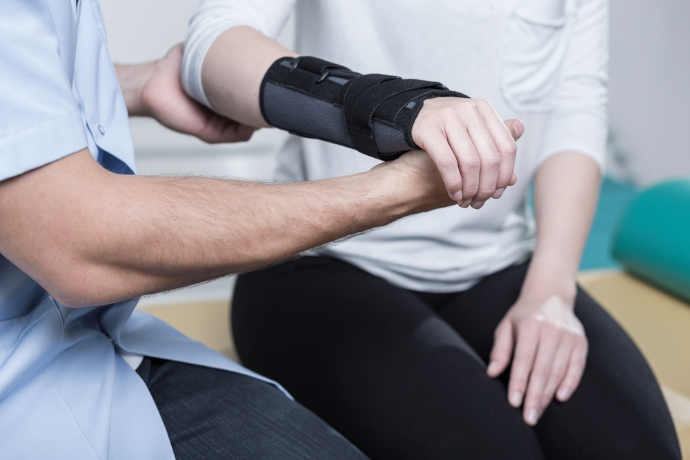 What is an OSHA Recordable Injury? Woman with arm in cast, seated with medical professional