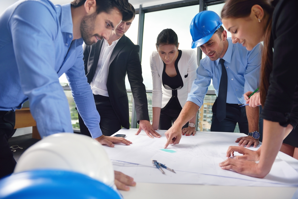 business people group on meeting and presentation  in bright modern office with construction engineer architect and worker looking building model and blueprint planbleprint plans for biofilter living wall