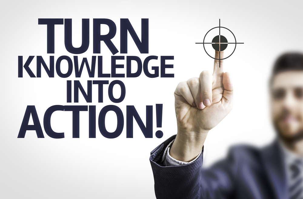 Business man pointing to transparent board with text Turn Knowledge Into Action!.jpeg