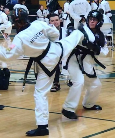 Hussey sparring in a tournament. Century Student Headgear, Gloves and Boots.