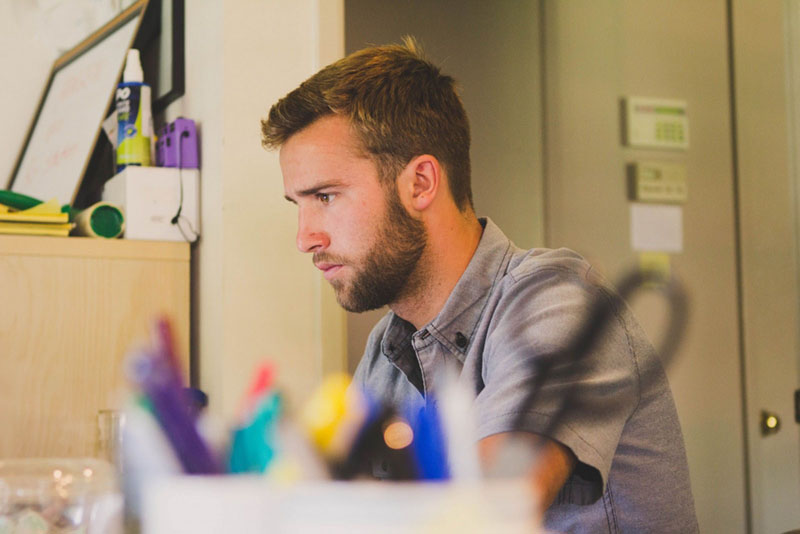 young-man-sitting-and-working-at-desk-1