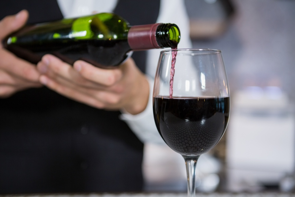 Mid section of bartender pouring red wine on glass in bar counter.jpeg