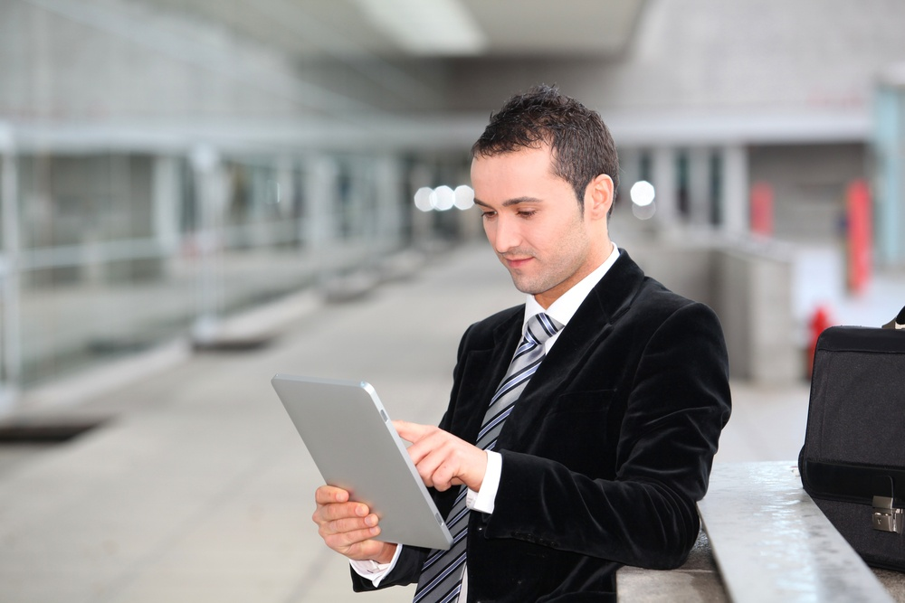 Salesman stannnding oustide with electronic tablet.jpeg