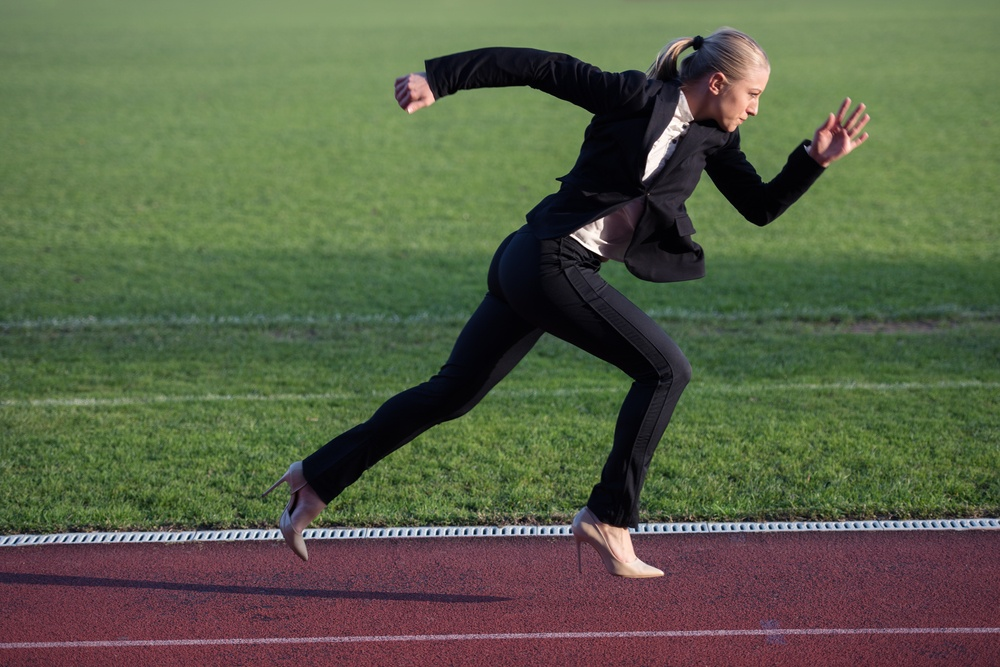business woman in start position ready to run and sprint on athletics racing track.jpeg