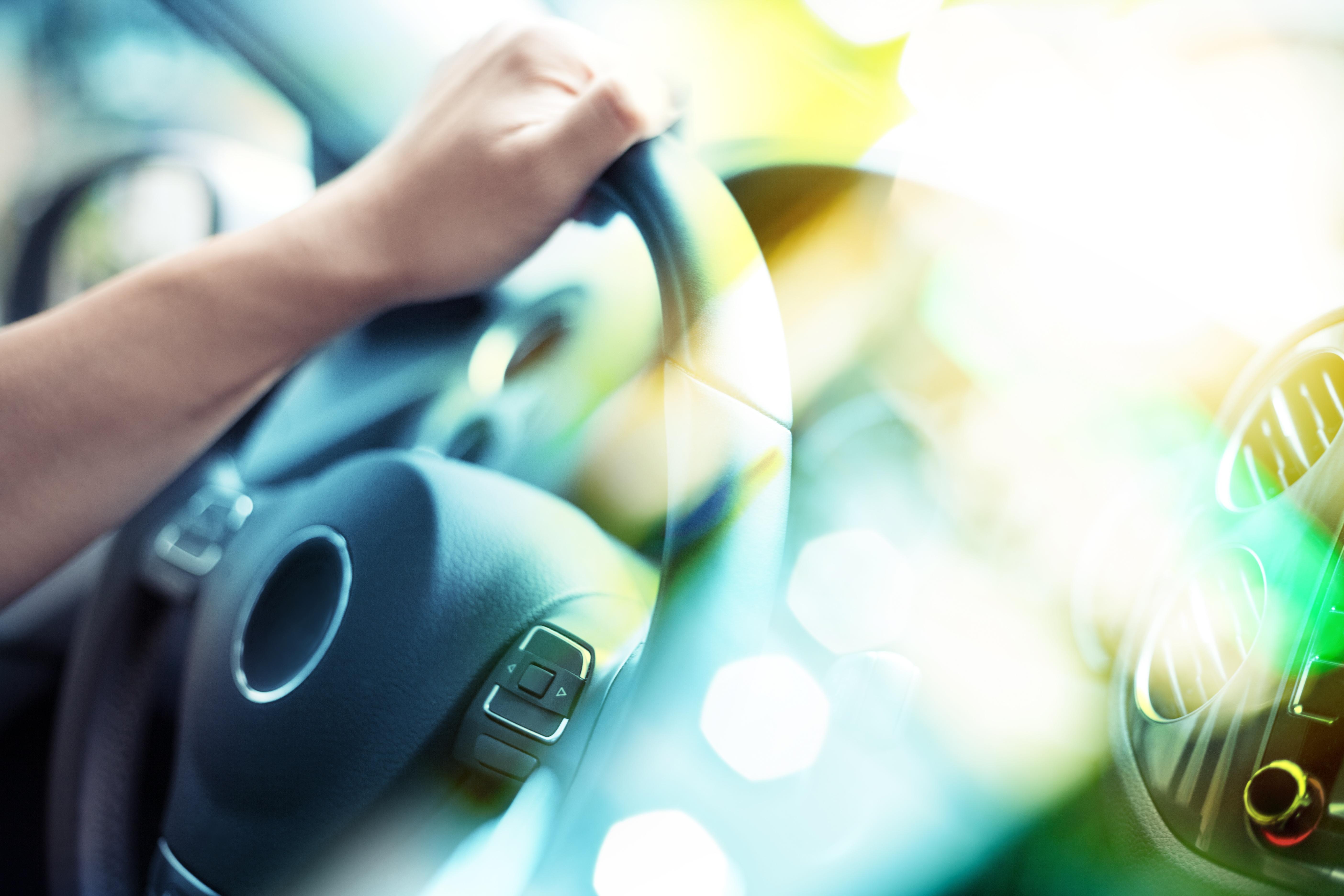 hand on steering wheel of car