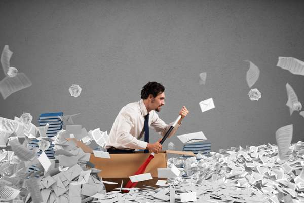 Employee in a box with an oar surrounded by papers