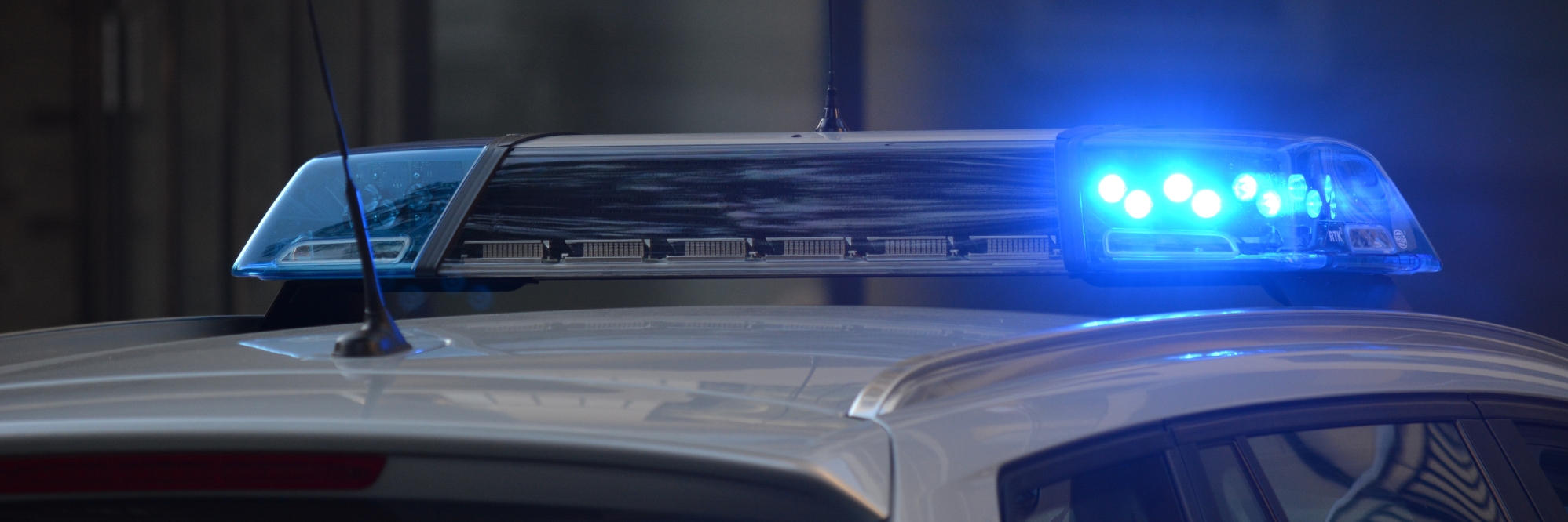 Police car with blue light on.