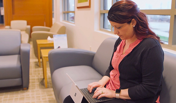 Image of woman completing hereditary cancer risk assessment questionnaire on tablet