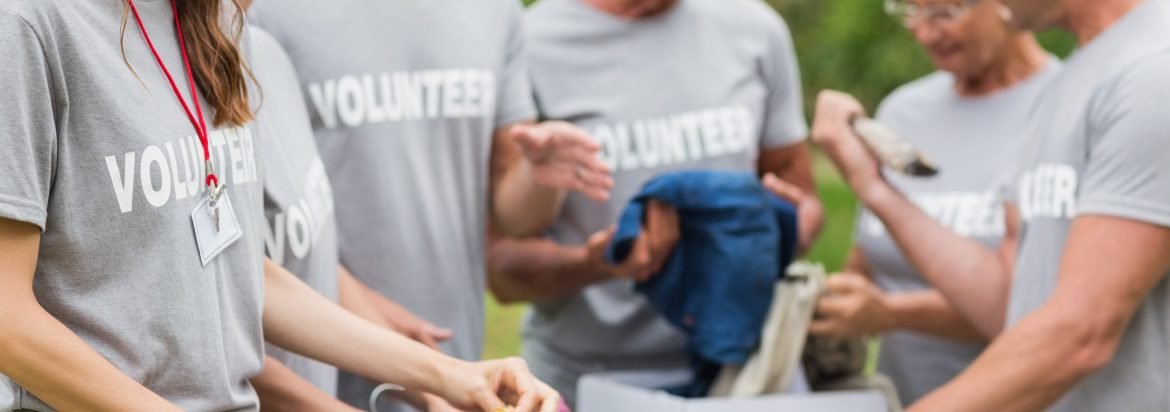 A close up image of people wearing volunteer t-shirts for charity.