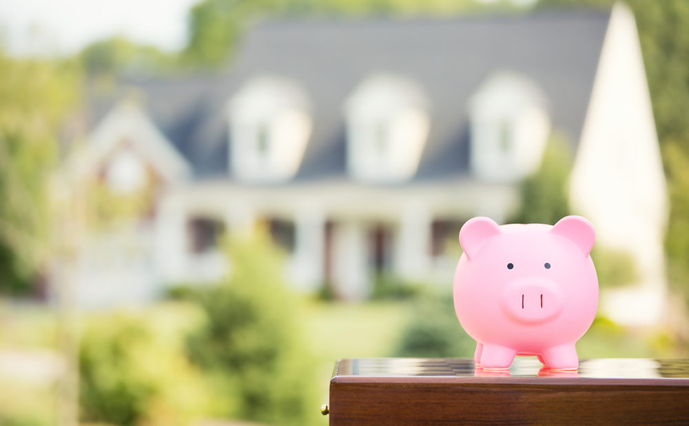 Real estate sale, home savings, loans market concept. Housing industry mortgage plan and residential tax saving strategy. Piggy bank isolated outside home on background. Focus on piggybank. Homeowner