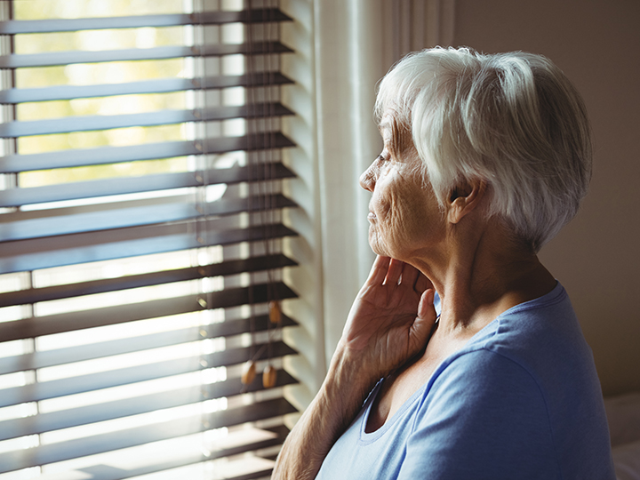 Older adult woman looking out of her window feeling stressed