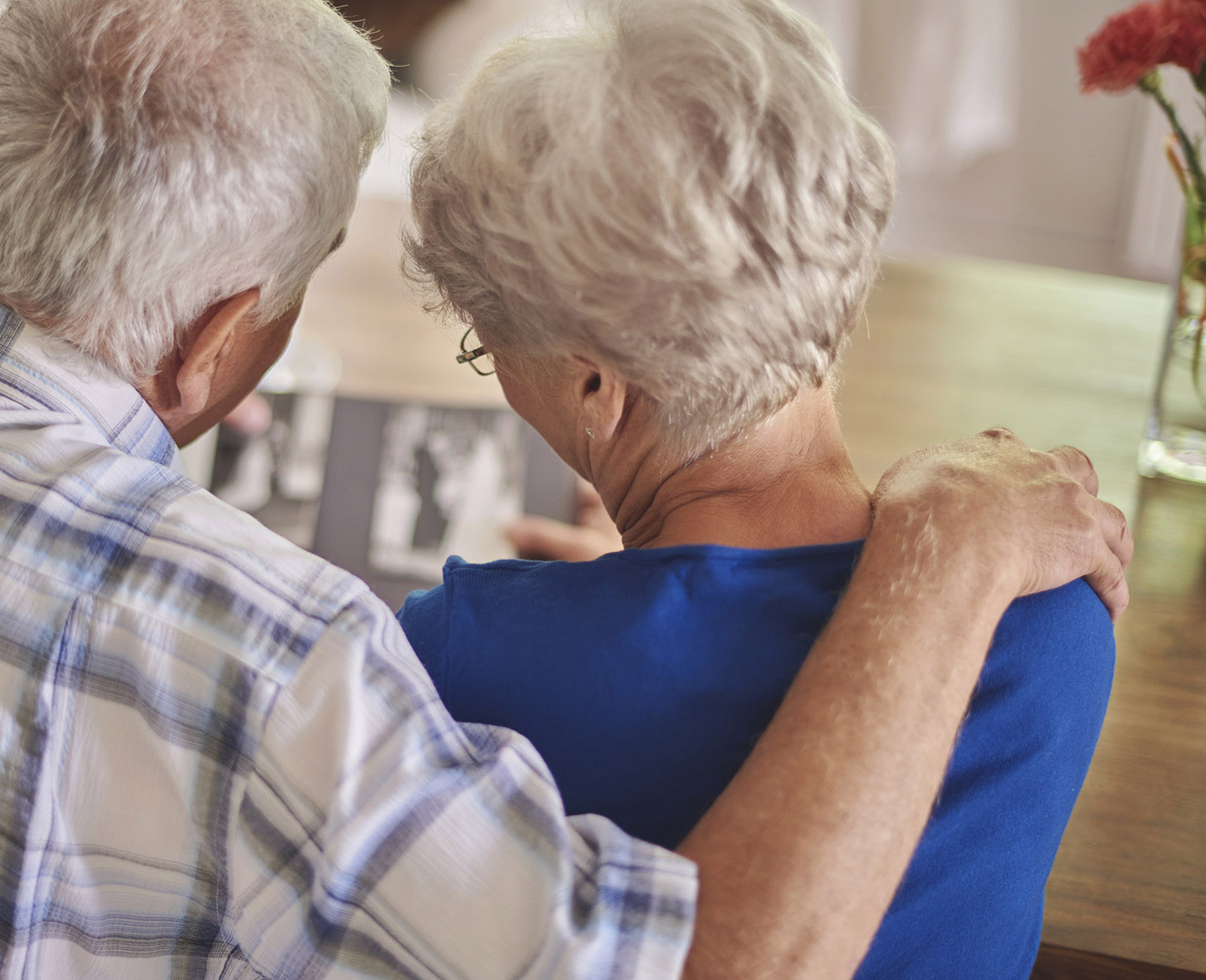 senior couple sharing a moment over memories while viewing a photo album