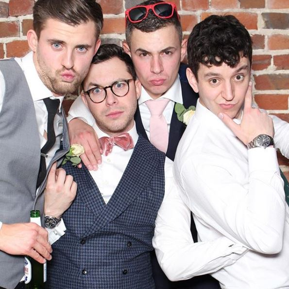 Groom and groomsmen in a photo booth