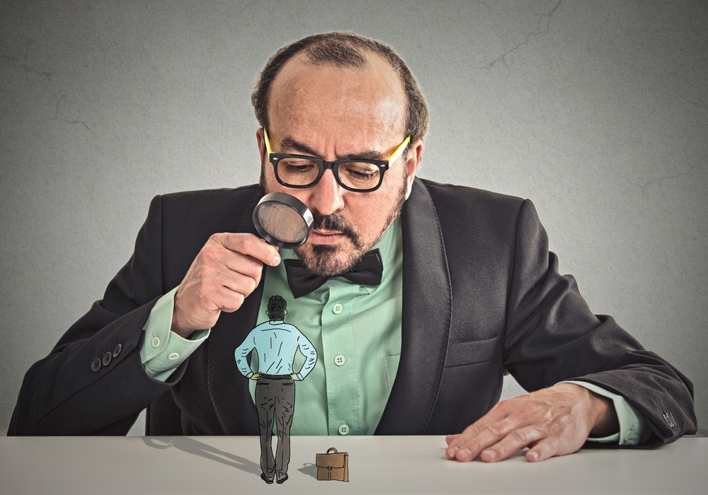 Curious corporate businessman skeptically meeting looking at small employee standing on table through magnifying glass isolated office grey wall background. Human face expression, attitude, perception.jpeg