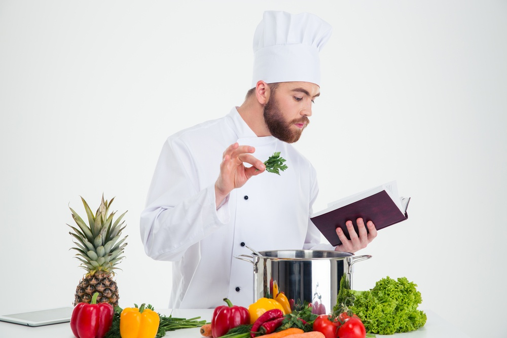 Portrait of a handsome male chef cook reading recipe book while preparing food isolated on a white background.jpeg