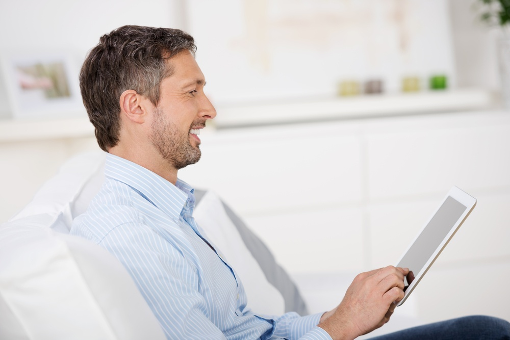 Side view of mature man reading ebook at tablet pc while sitting on sofa at home.jpeg