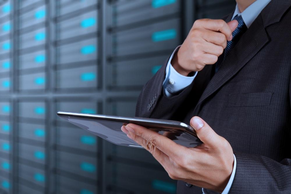 businessman hand using tablet computer and server room background.jpeg