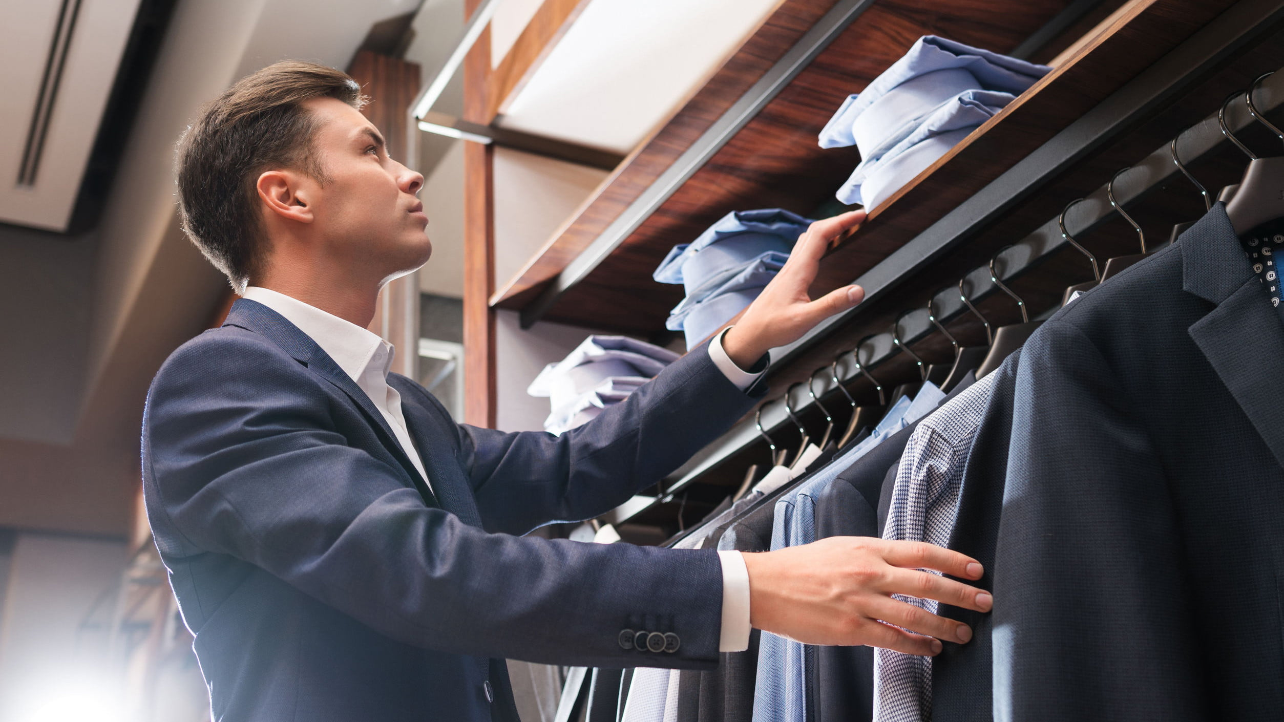stock-man-buying-suit-in-store-2507x1410