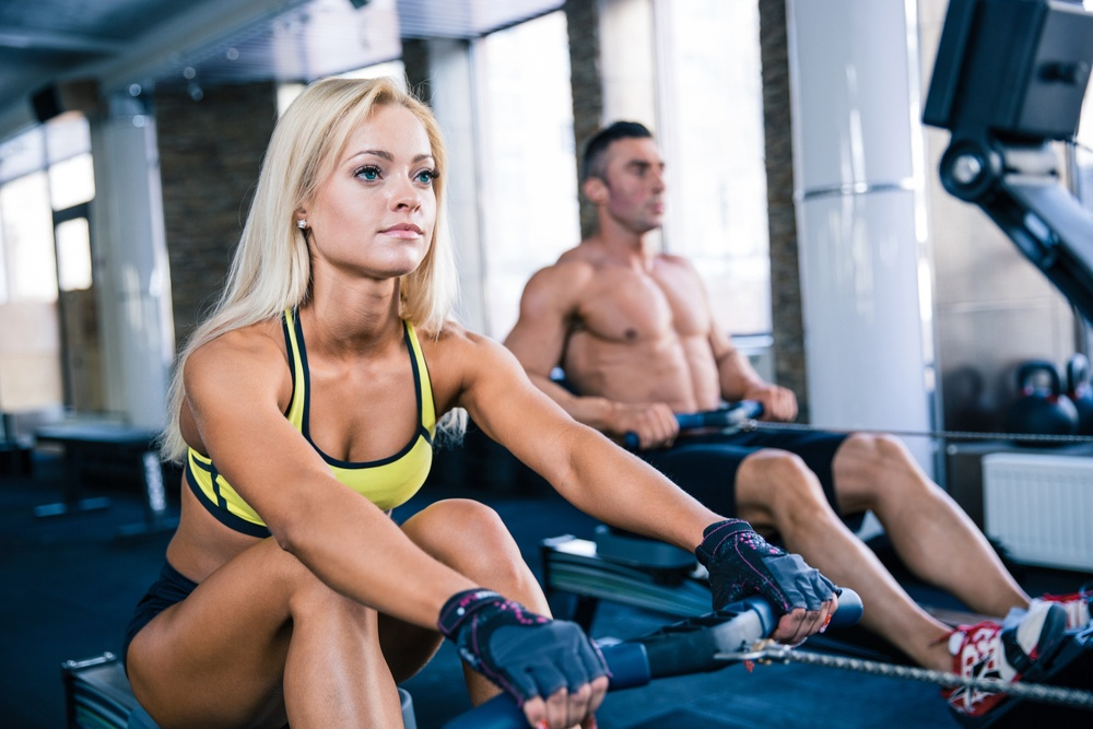 Muscular man and sporty woman workout on training simulator in crossfit gym.jpeg