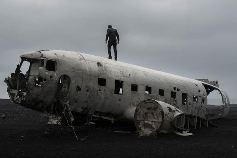 Person standing on top of an airplane wreck