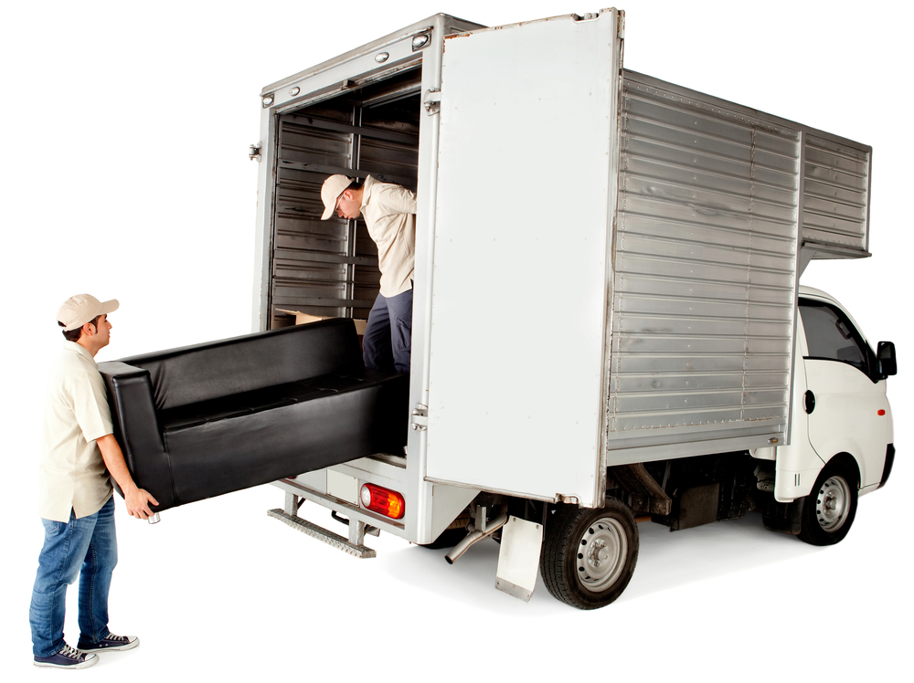 Delivery men loading a sofa in a truck - isolated over white