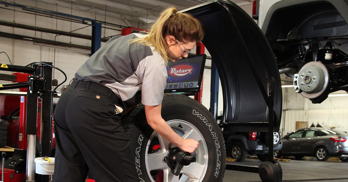 an automotive technician sets a tire on a tire balancing machine