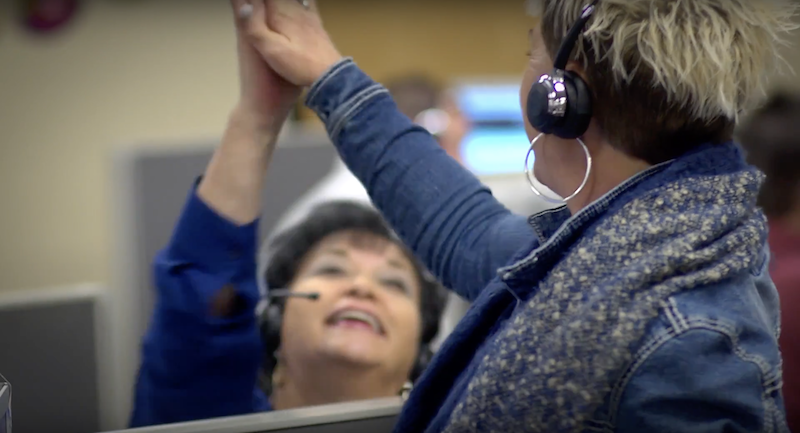 Gold Mountain Communications has partnered with DailyPay to offer its employees instant access to earned wages. An image of two women giving high five.