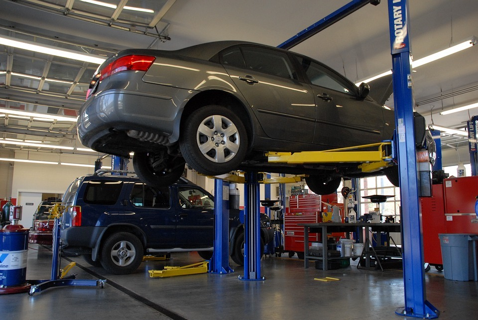 An image of two cars in an auto repair shop. When unexpected car repair expenses arise, employees with instant access to earned wages can cover unexpected expenses.