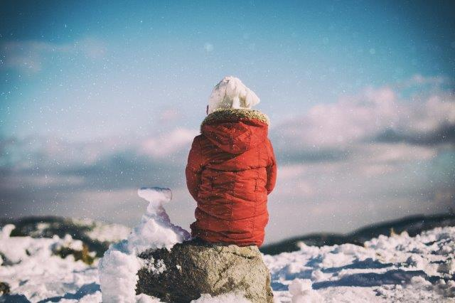 Girl in winter jacket sitting on a rock