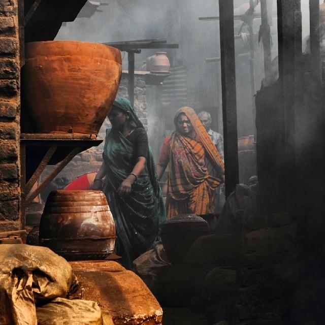Indian women walking through pottery.