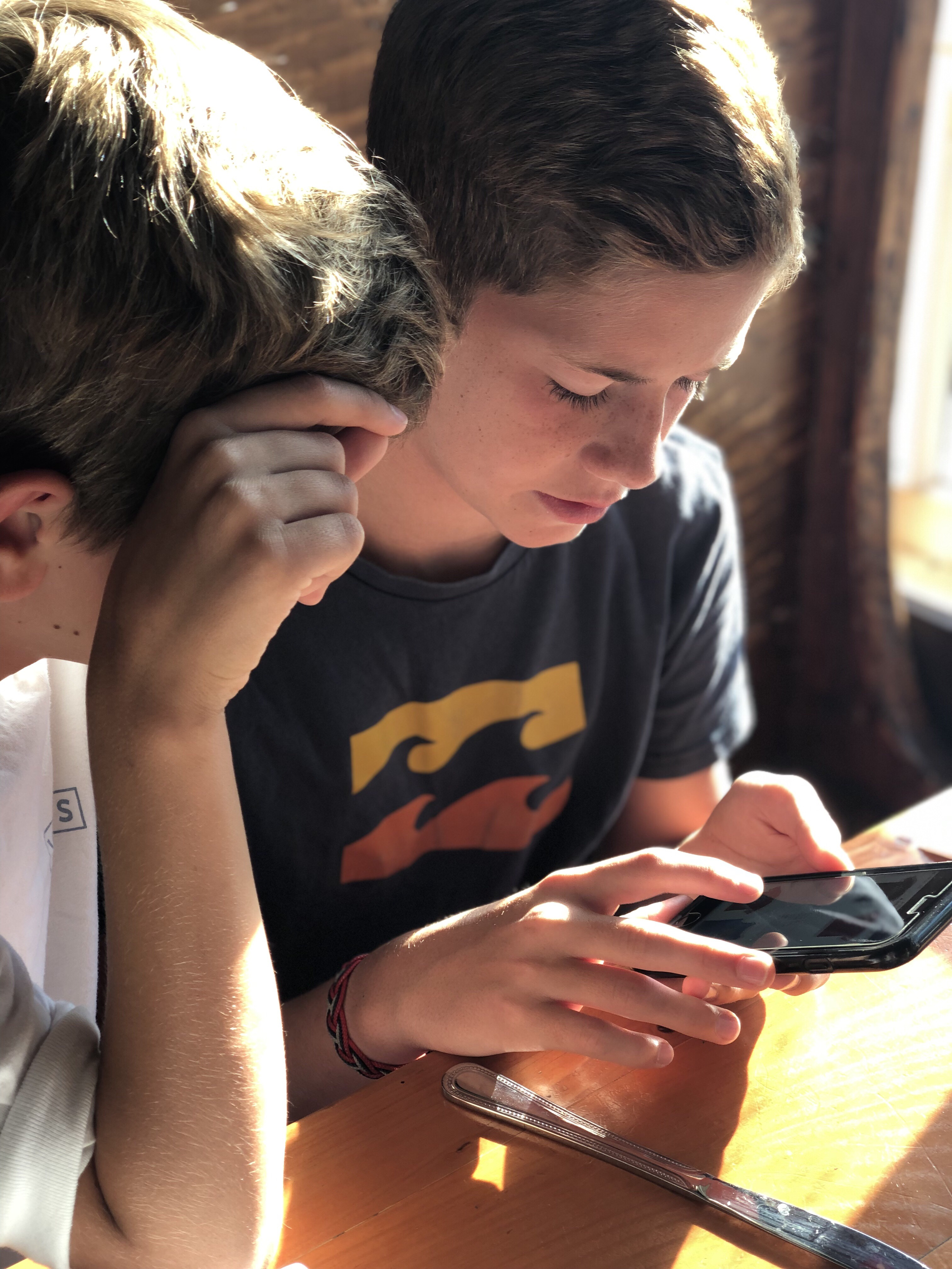 Two tween boys looking at a cell phone