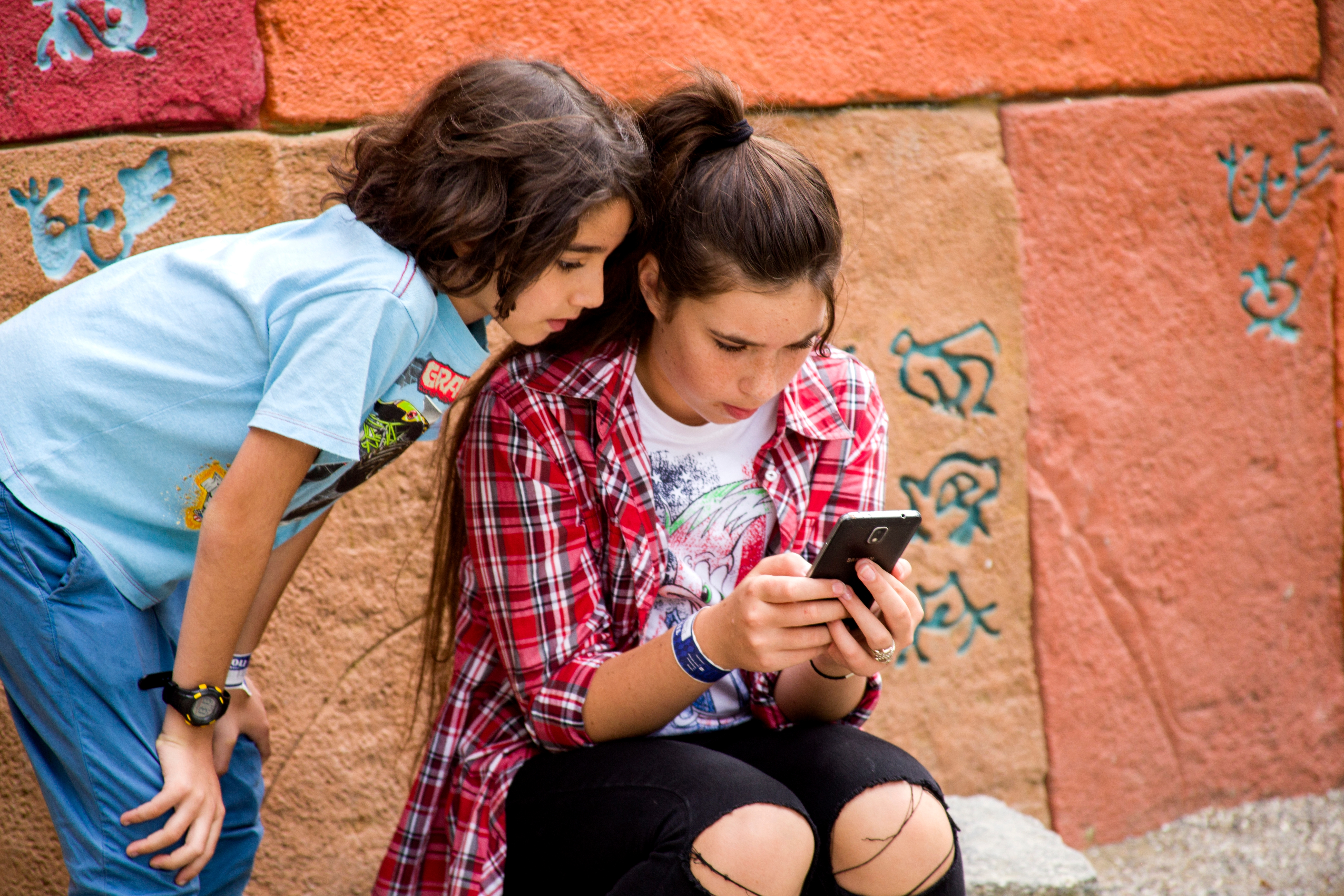 Teen sister and tween brother view smartphone near colorful wall.