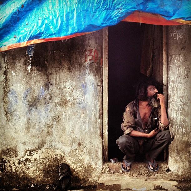 Indian man waits in his doorway