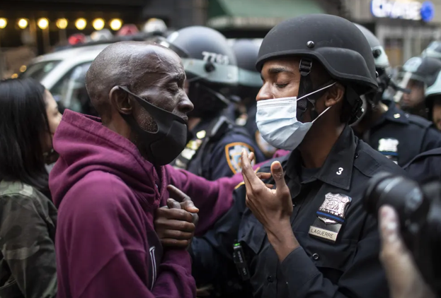 A protester and a police officer hold hands in the middle of a standoff, New York