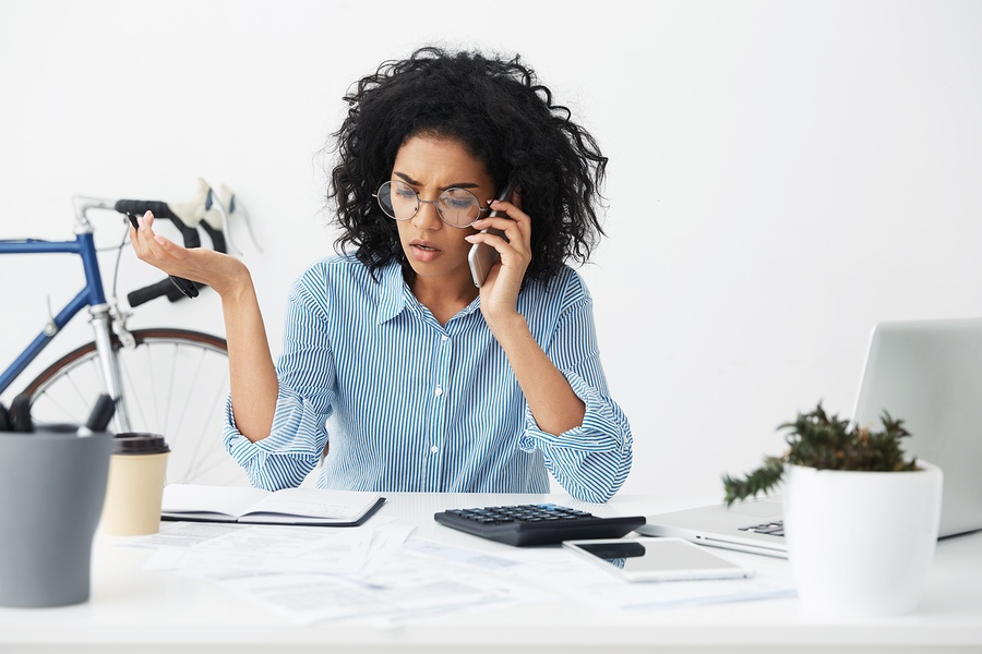 Stress signs African American women trying to multitask at desk