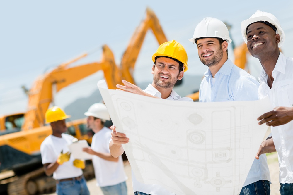 Group of workers at a construction site holding blueprints