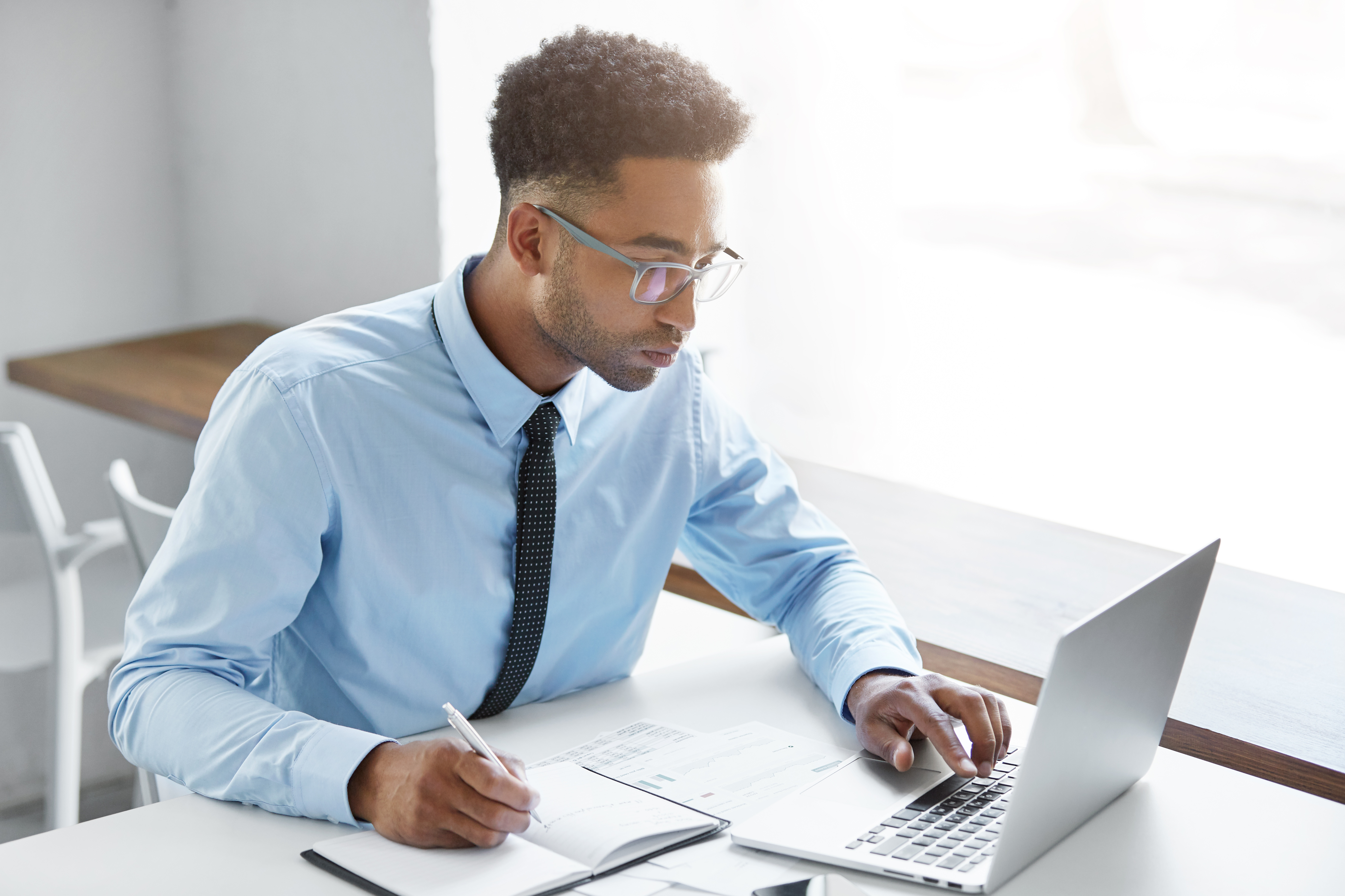 Male worker site in C-style blue shirt at office desk
