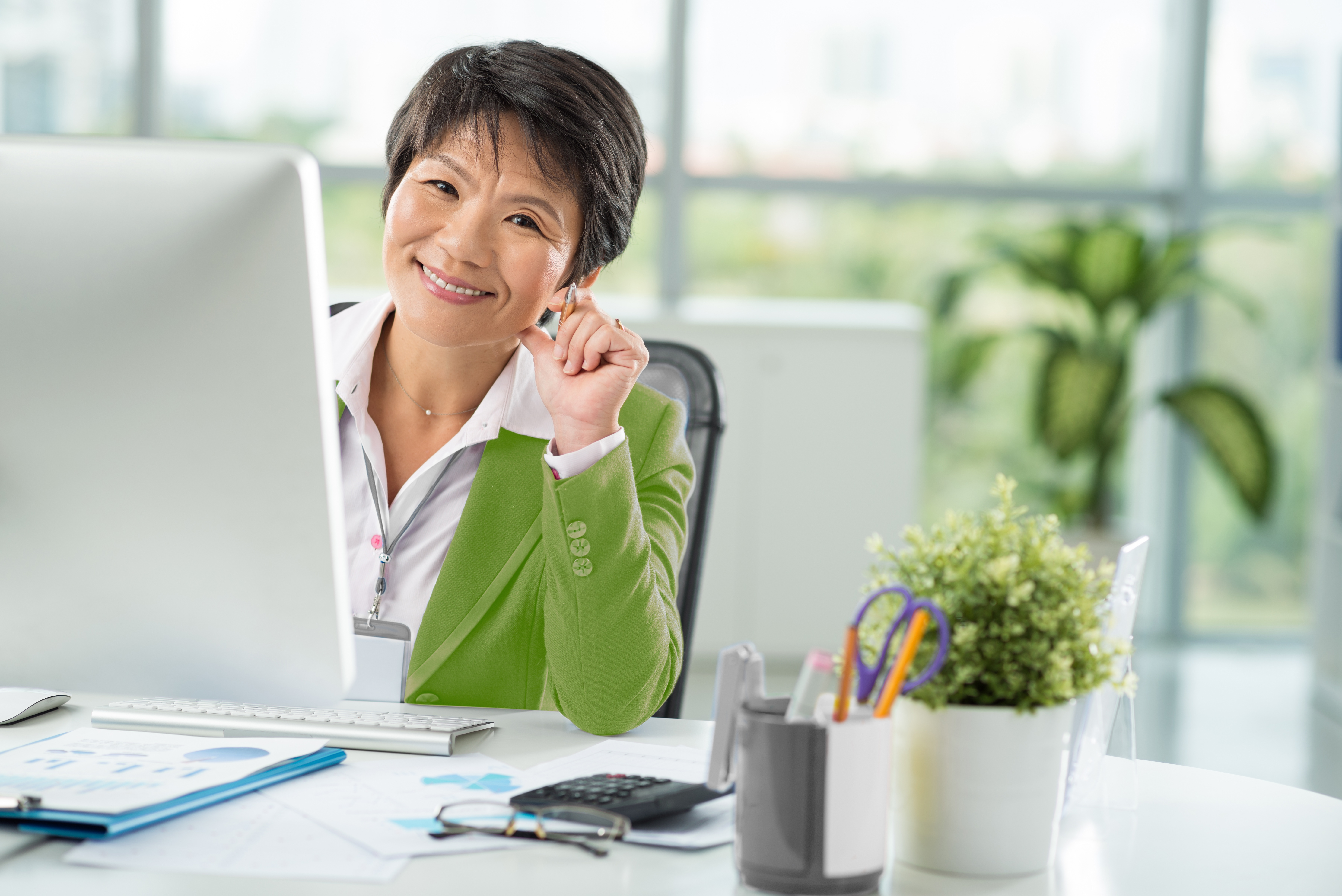 S-style green sweater female worker sitting at computer