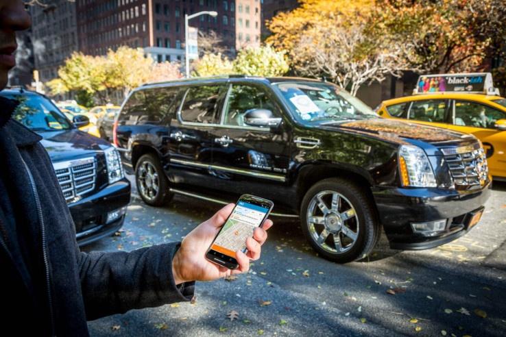 man-holding-phone-ordering-via-ridehail-service-black-suv
