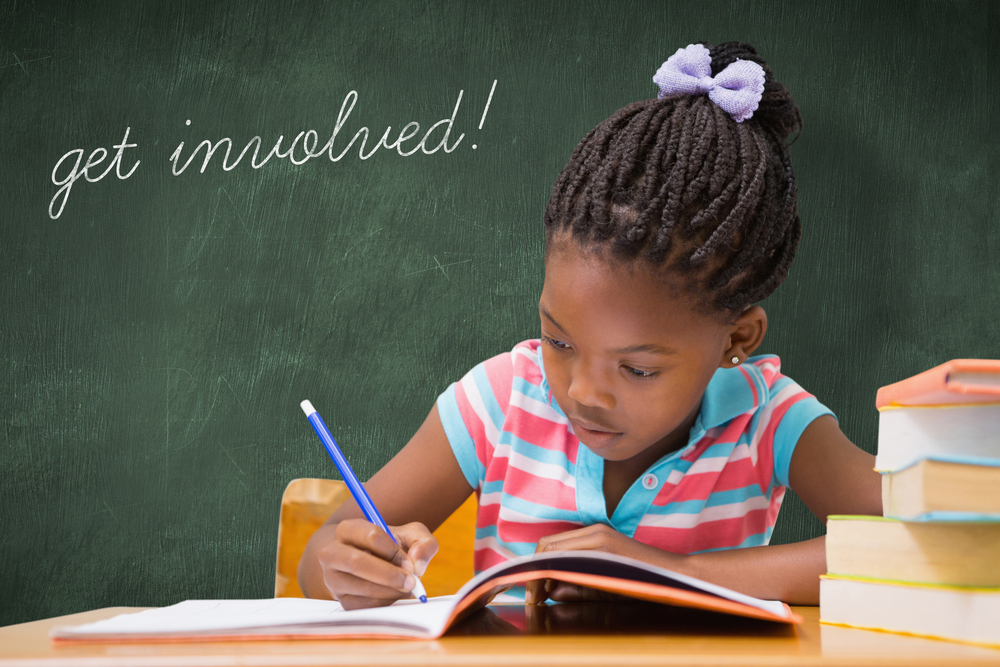 The word get involved! and cute pupils writing at desk in classroom against green chalkboard