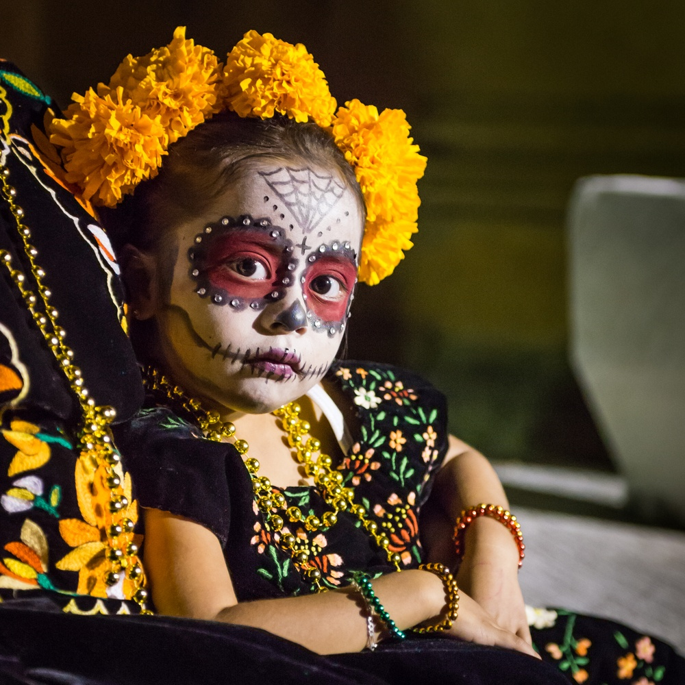 little girl with face painted on day of the dead in mexico
