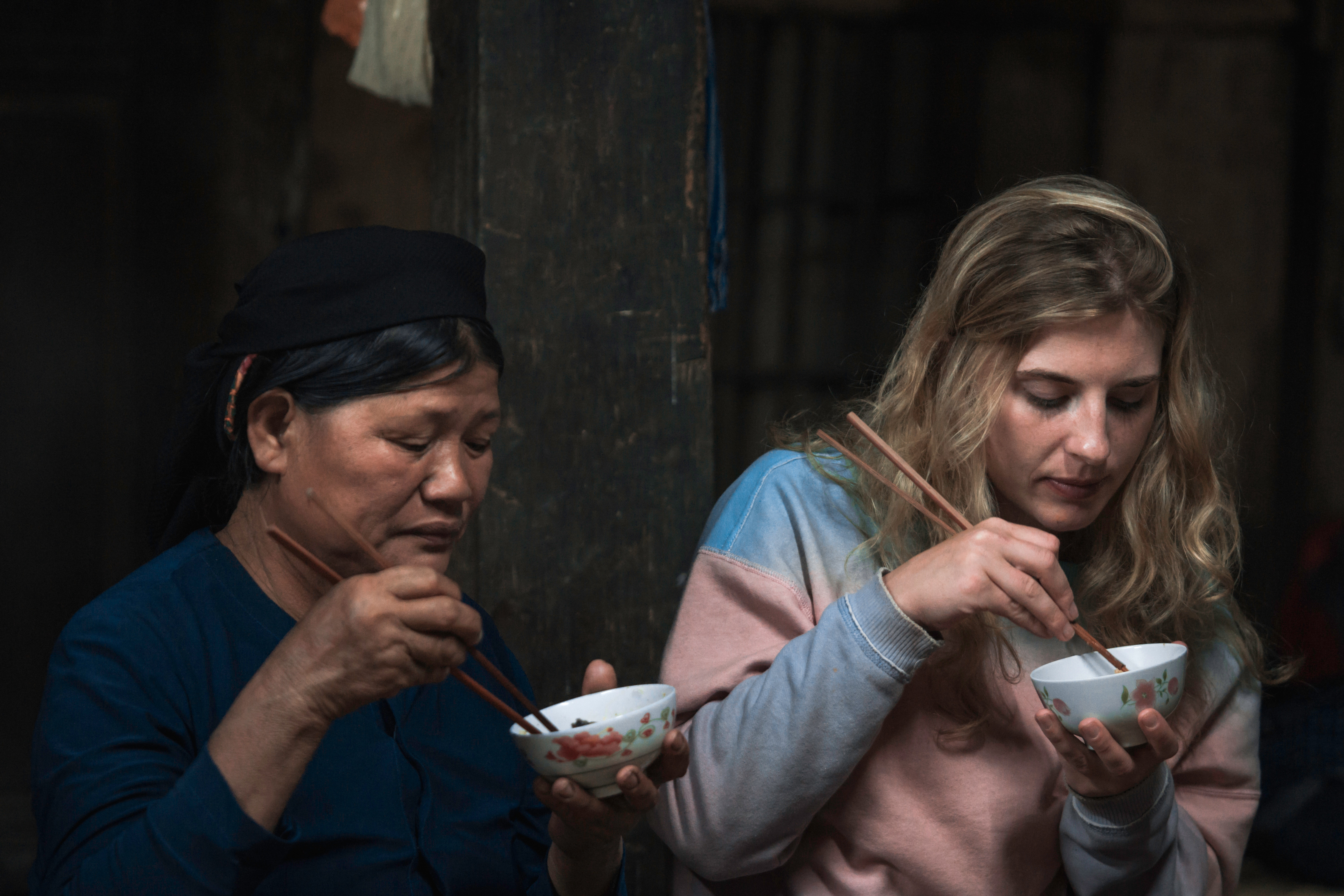 Vietnamese woman and foreign girl eat together with chopsticks, solo travel
