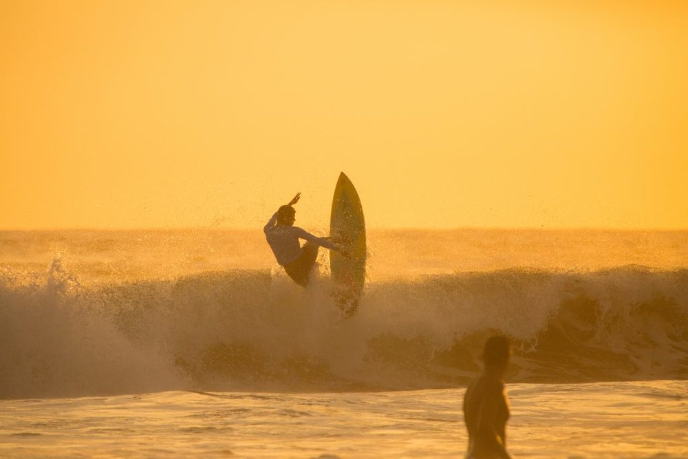 surfer in the sunset in todos santos california