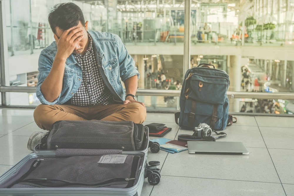 frustrated guy at the airport not knowhing what to do