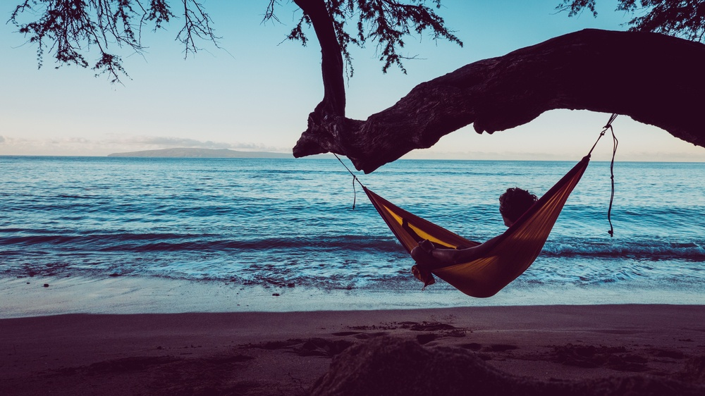 guy chilling on a hammock on a beach looking at the ocean