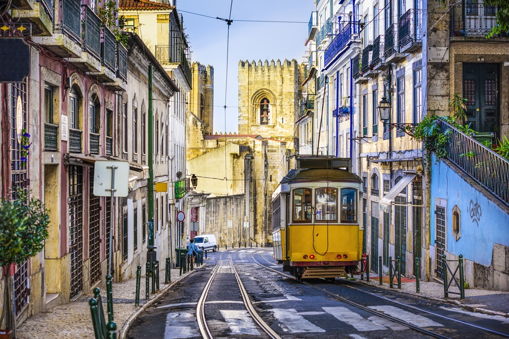 classic street view in Lisbon, Portugal with a tram riding through it
