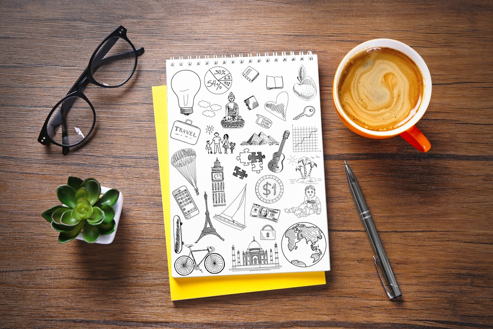 a page with travel sketches on it and glasses next to it on a wooden table