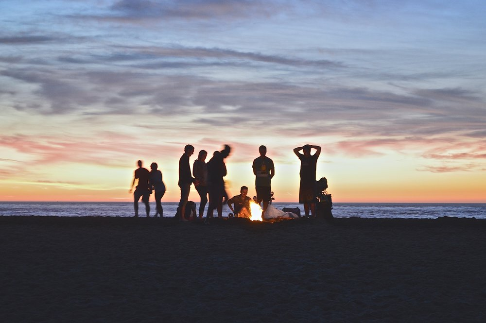group of friends having a bonfire on the beach